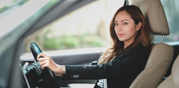Professional businesswoman looking while driving the car