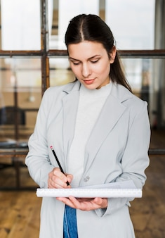 Professional businesswoman writing on diary
