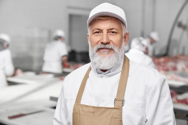 Professional butcher, elderly man in white uniform posing.