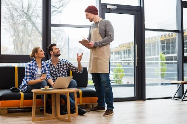 プロのカフェサービス。顧客を見て、注文を待っている間彼のメモを保持して喜んで幸せなナイスマン