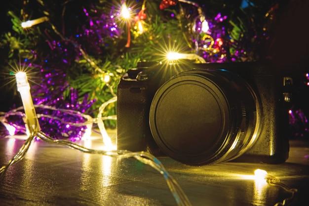 새해 또는 크리스마스 선물로 전문 카메라. 이 카메라는 밝은 조명 아래 있는 크리스마스 트리 아래에서 충전할 수 없습니다.