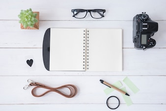 Professional camera; blank spiral notepad; spectacle; sticky notes; belt; pen; heartshape and succulent plant on white wooden table