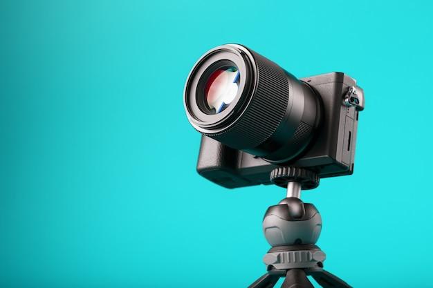 青色の背景に、三脚にプロ用カメラ。ブログまたはレポート用にビデオと写真を記録します。