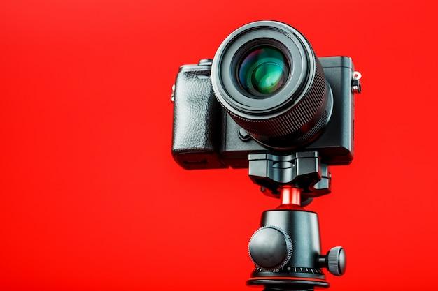 赤の背景に、三脚にプロ用カメラ。ブログ、ルポルタージュのためにビデオと写真を記録する
