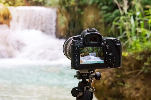 Professional camera photographing on a long exposure of a beautiful waterfall kuang si in laos. slr camera on a tripod shooting a video of the water fall. wildlife photography.