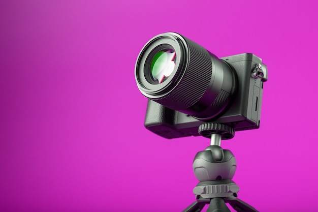 Professional camera on a tripod, on a pink background. record videos and photos for your blog or report.
