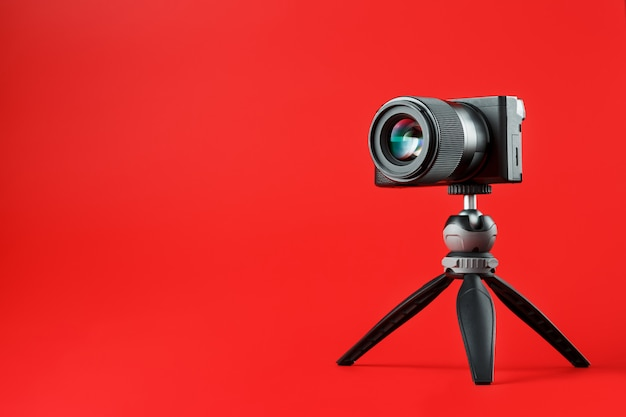Professional camera on a tripod, on a red background. record videos and photos for your blog, reportage