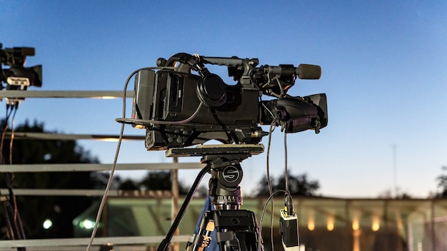 A professional camera on a tripod with a lot of cables at dusk