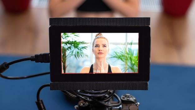 スポーツウェアの若いブロンドの女性を記録する外部ディスプレイ付きのプロのカメラ