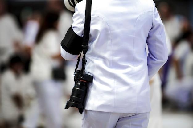Профессиональный оператор обратно висящий ремень и беззеркальная камера с размытым фоном толпы.