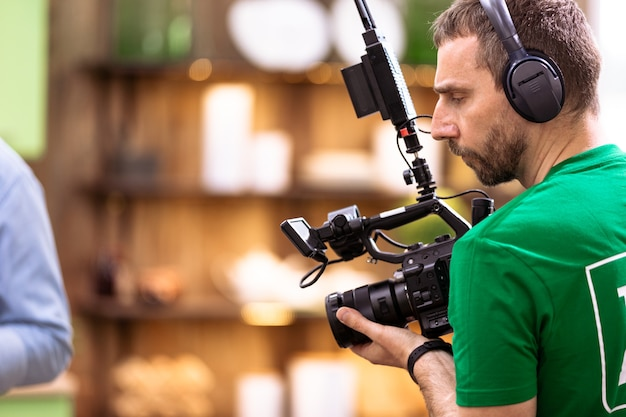 A professional cameraman is filming on a video camera
