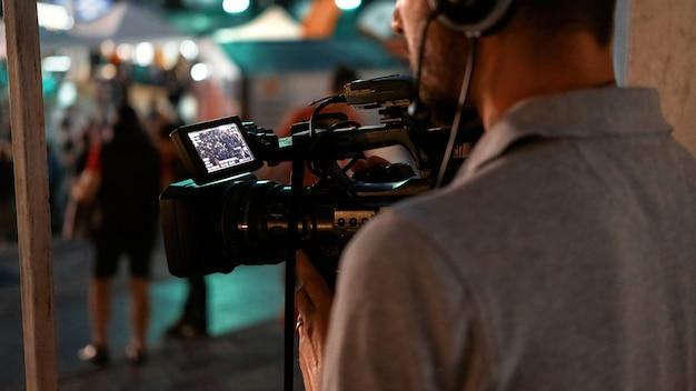夜に公共の場所でサッカーを見ている人々を記録するプロのカメラマン