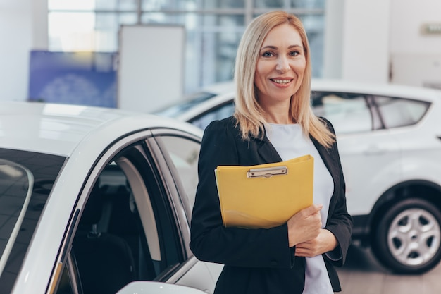 Professional car dealer posing at auto showroom smiling to the camera