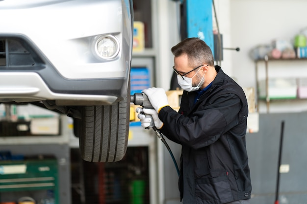 자동차 정비 및 자동 서비스 차고에서 자동차 바퀴를 변경하는 전문 자동차 정비사
