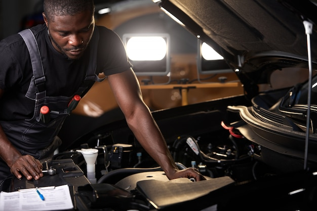 Professional car mechanic is examining engine under the hood at auto repair shop