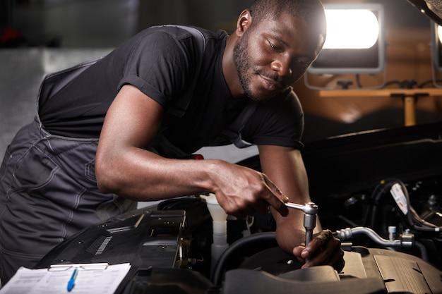 전문 자동차 정비공은 자동차 수리점에서 후드 아래에서 엔진을 검사하고 있습니다.