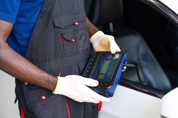 Professional car mechanic repair service and checking car engine by diagnostics software computer.