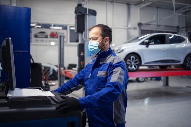 コロナウイルスのパンデミック時に車両のワークショップで働くフェイスプロテクションマスクを備えたプロの自動車整備士。