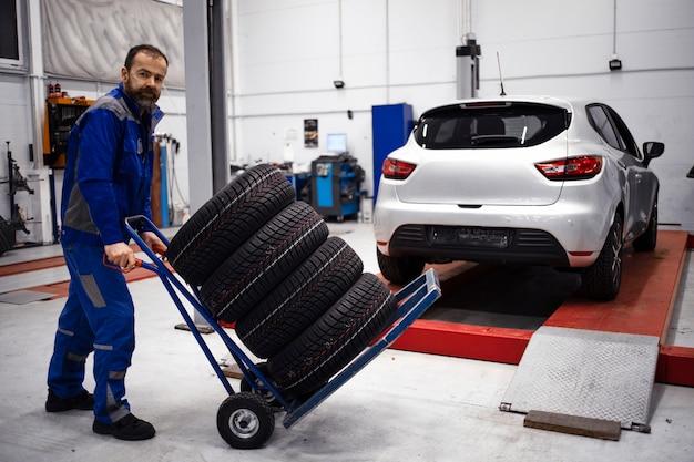 車でワークショップに立っている新しいタイヤのセットを持つプロの自動車整備士。