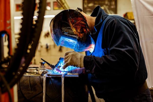 Professional car mechanic working in auto repair service on argon gas cutting machine