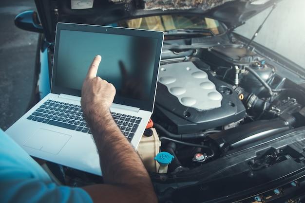 Профессиональный автомеханик, работающий в автосервисе с ноутбуком на автомобиле