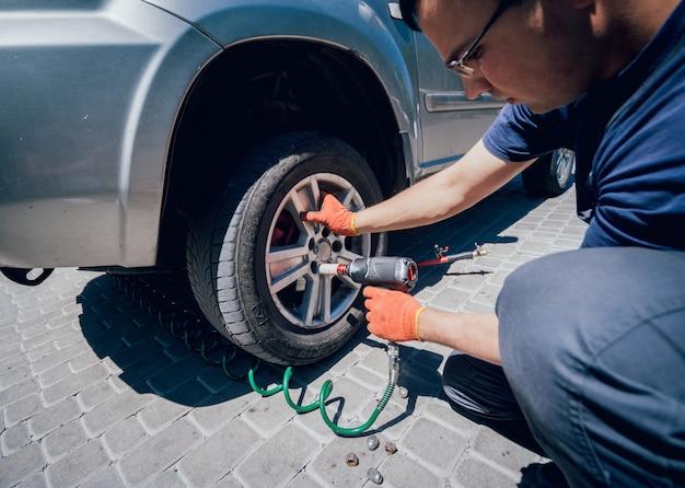 Профессиональный автомеханик работает с пневматическим гаечным ключом в автосервисе.