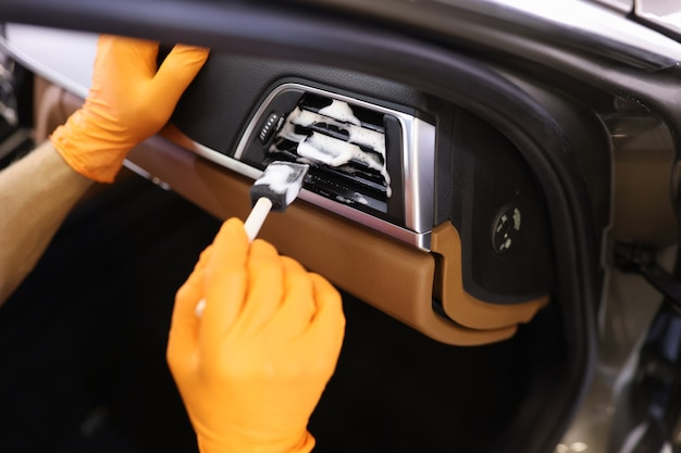 Professional car service worker in protective gloves cleans car grill with foam and brush car