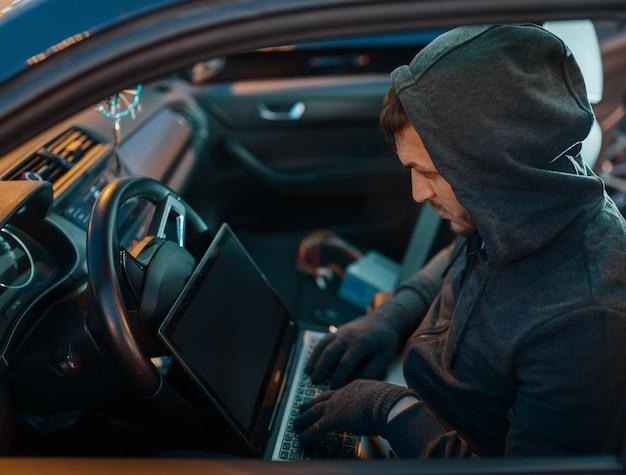 Профессиональный угонщик с системой безопасности взлома ноутбука, преступный образ жизни. мужчина-грабитель в капюшоне открывает автомобиль на стоянке. автомобильное ограбление, автомобильное преступление Premium Фотографии