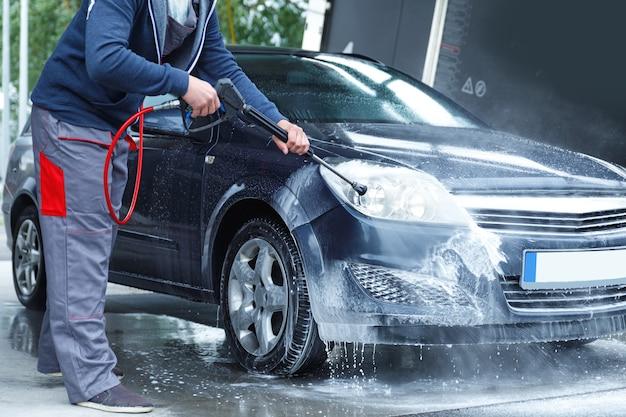 プロの洗車員がクライアントの車を洗っています