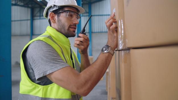 Профессиональный грузовой рабочий разговаривает по рации, чтобы связаться с другим рабочим