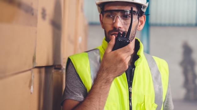 전문화물 작업자가 휴대용 라디오로 다른 작업자에게 연락