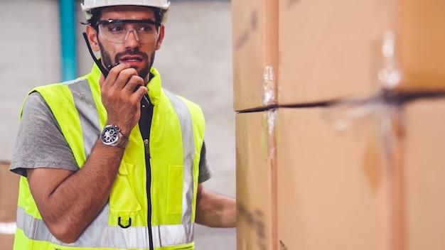 プロの貨物労働者が携帯ラジオで話し、別の労働者に連絡する