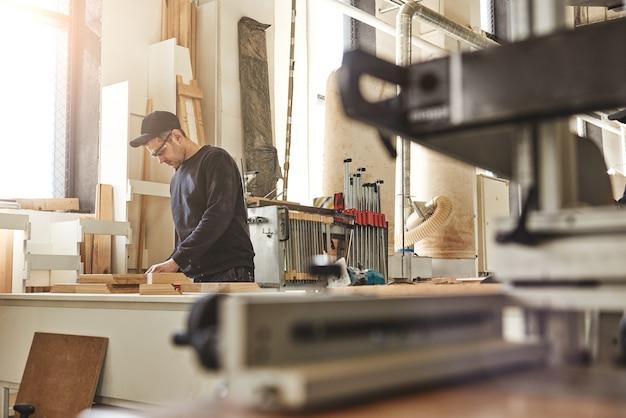 Профессиональный плотник за работой, он вырезает дерево с помощью деревообрабатывающего инструмента.