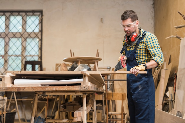 Профессиональный плотник резает деревянную доску ручной пилой в мастерской