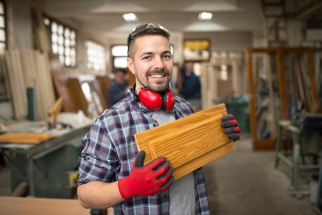Профессиональный плотник держит древесный материал в столярной мастерской