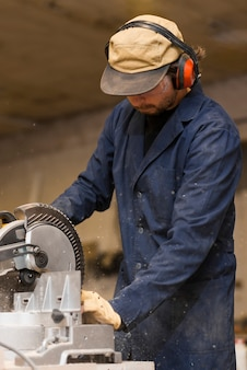 Professional carpenter uses circular saw in workshop