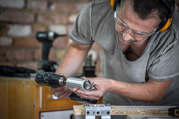 ヒンジドリルで作業し、木材で作業するプロの大工