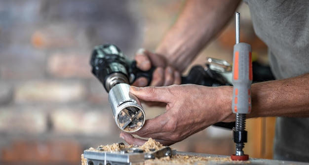 Carpentiere professionista che lavora con un trapano a cerniera, lavora con il legno