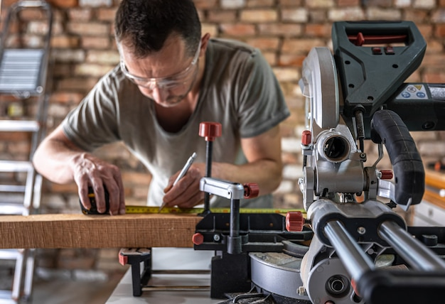A professional carpenter works with a circular saw miter saw in a workshop.