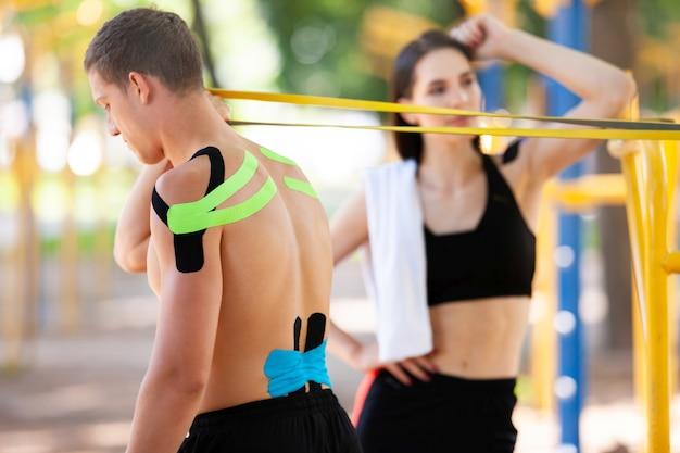 Профессиональные кавказские спортсмены, красивый мужчина, тренирующийся с использованием группы сопротивления, и брюнетка женщина с кинезиологической тейпом на телах, позируют на спортивной площадке, глядя друг на друга.