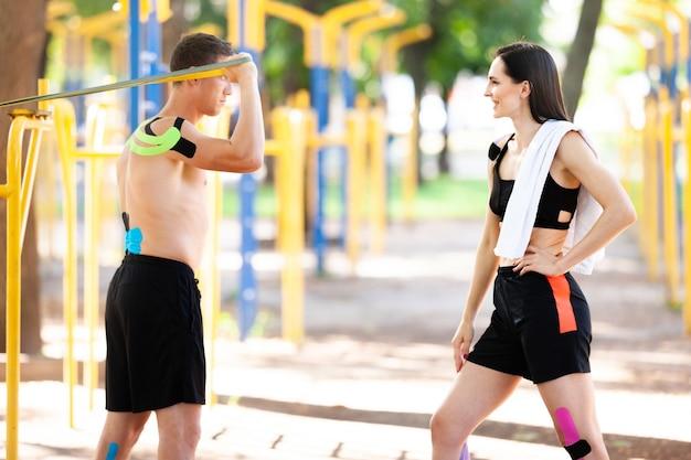 Профессиональные кавказские спортсмены, красивый мужчина, тренирующийся с использованием группы сопротивления, и брюнетка с кинезиологической тейпом на теле