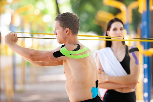 プロの白人アスリートのハンサムな男性がレジスタンスバンドを使用してトレーニングし、ブルネットの女性が体に運動学的なテーピングを施している