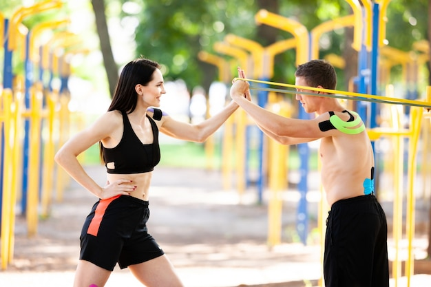 Professional caucasian athletes, handsome man training using resistance band and brunette woman with kinesiological taping on bodies, posing at sports ground, looking at each other.