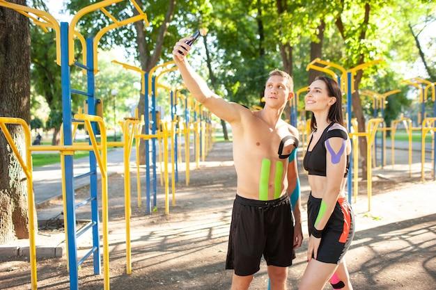 신체에 탄력적인 테이핑을 하는 백인 전문 운동선수, 잘생긴 남자, 갈색 머리 여성, 운동장에서 포즈를 취하고 휴식을 취하고 스마트폰으로 셀카를 찍습니다.