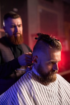 Professional caucasian barber master hairdresser does hairstyle