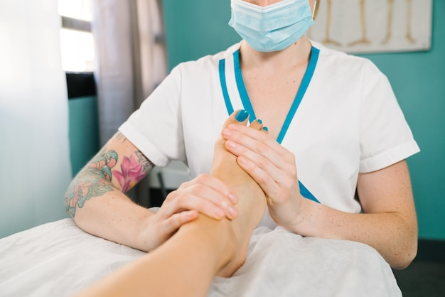 Professional caucasian woman giving a physiotherapeutic foot massage wearing a face mask due to the covid 19 coronavirus pandemic