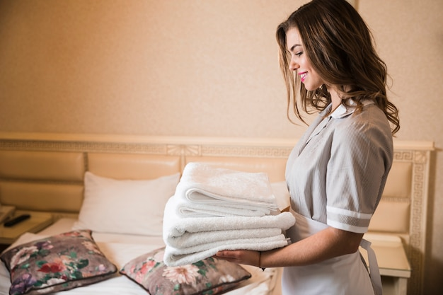 Professional chambermaid holding white pile of clean folded towels in bedroom