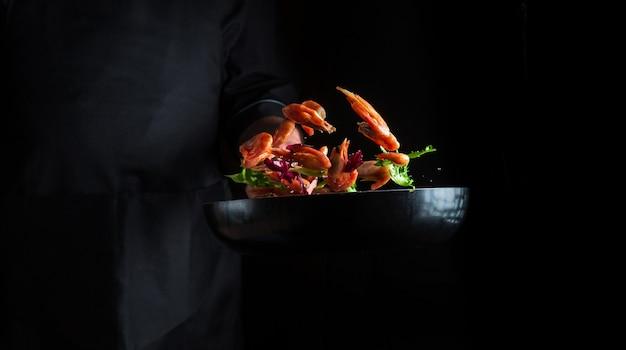 전문 요리사는 야채와 함께 냄비에 새우를 요리합니다. 어두운 배경에서 해산물, 건강한 채식주의 음식, 음식을 요리하세요. 움직임이 멈춥니다. 무료 광고 공간