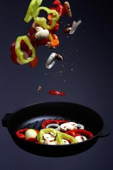 Профессиональный повар. готовит овощи на сковороде, азиатская кухня. книга рецептов. вкусная здоровая еда