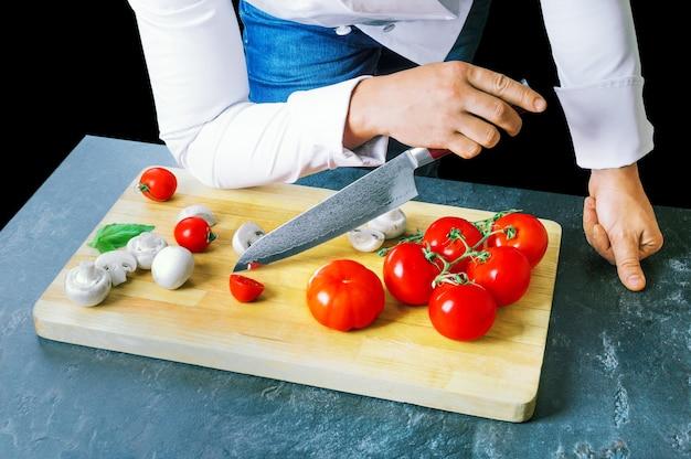 プロのシェフがダマスカス鋼の鋭利なナイフで野菜を切ります。ミクストメディア